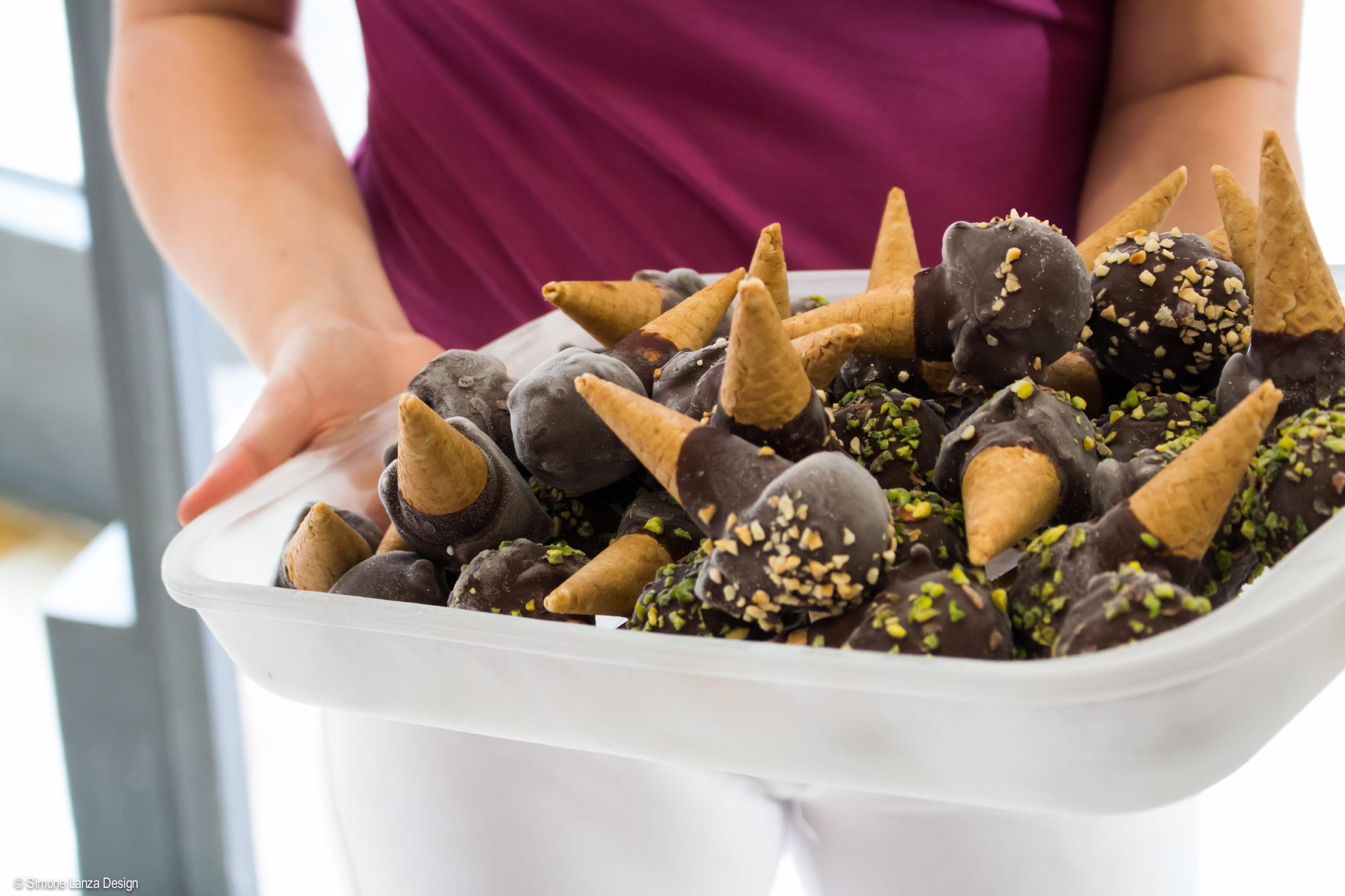 Ragazza tiene in mano un vassoio di mini coni ricoperti di cioccolato e granella, realizzati dalla gelateria Terra e Cuore